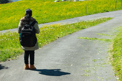 Female traveller with backpack walking along trail of green road. Female traveller with backpack walking along trail of road with green grass on both sides. The Royalty Free Stock Images