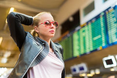 Female traveller checking flight departures board. Stock Photos