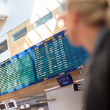 Female traveller checking flight departures board. Royalty Free Stock Photo