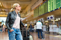 Female traveller checking flight departures board. Royalty Free Stock Images