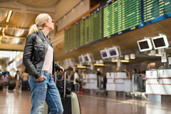 Female traveller checking flight departures board. Royalty Free Stock Photography