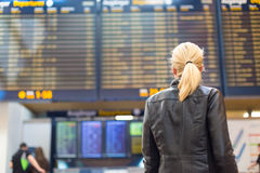 Female traveller checking flight departures board. Royalty Free Stock Image