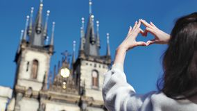 Female traveller enjoying amazing historic castle making gesture heart love by hands back view. Adorable young woman contemplative to beautiful architecture stock video