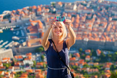 Female traveller make a selfy photo to the phone. Female traveller make a selfy photo against the background of the old city of Dubrovnik from the mountain to Royalty Free Stock Images