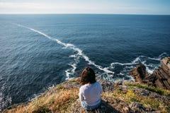Female traveller overlooks ocean cliffs stock photography