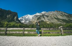 Female traveller posing in front of mountain view of Alps Stock Photos