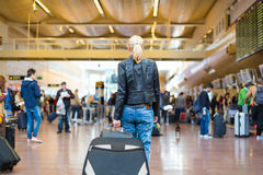 Female traveller walking airport terminal. Casually dressed young stylish female traveller walking the airport terminal hall   draging suitcase and a handbag Stock Image
