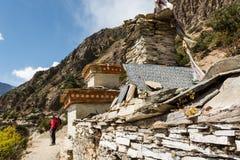 Female trekker passing buddhist writings. Stock Photography