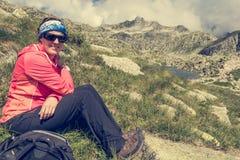 Female trekker resting on mountain meadow. Royalty Free Stock Photo