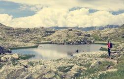 Female trekker walking along mountain lake. Royalty Free Stock Image