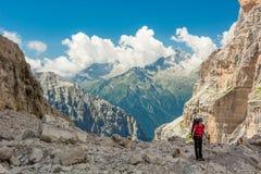 Female trekker walking along mountain valley. Trekking Brenta Dolomites, Sentiero delle Bocchette Alte Royalty Free Stock Images