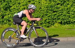 Female triathlete on Cycling stage. Royalty Free Stock Photo