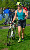 Female triathlete at end of cycling stage with bicycle. Stock Images