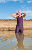 Female triathlete entering the water Royalty Free Stock Image