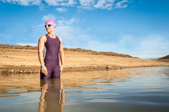 Female triathlete entering the water Stock Images