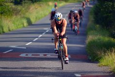 Female Triathlete on road cycling stage of triathlon. Royalty Free Stock Photos