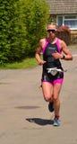 Female triathlete on running stage of triathlon. Stock Photo