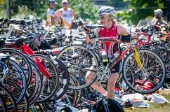 Female triathlon competitor places bike back in her rack. VICTORIA, CANADA JUNE 14, 2015 Female triathlon competitor places bike back in her rack during the Stock Images
