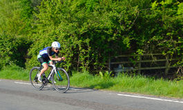 Female triathlon  competitor on road cycling stage. Stock Photos