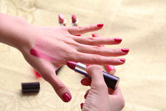 Female trying different shades of lipstick on her. A female is trying three different shades of lipstick on her hand to see which matches the skin colour when Stock Image