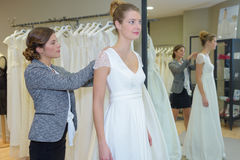 Female trying wedding dress in shop with shop assistant Royalty Free Stock Photo