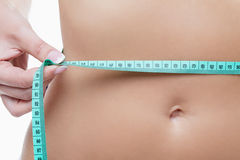 Female tummy with tape measure Royalty Free Stock Image