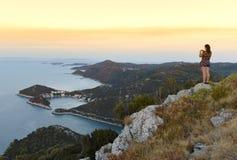 A female turist makes a photo on a smartphone on the island of L. Astovo, Croatia Stock Images