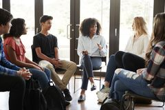 Free Female Tutor Leading Discussion Group Amongst High School Pupils Stock Photo - 127000500