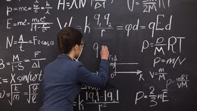 Female tutor writing formula on chalkboard, mathematics lecture, exact sciences. Stock footage stock footage