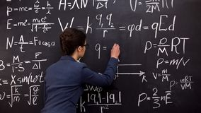 Free Female Tutor Writing Formula On Chalkboard, Mathematics Lecture, Exact Sciences Stock Images - 157891304