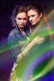 Female twins in colored light stripes. Female twins, studio shooting with light painting Stock Images