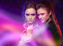 Female twins in colored light stripes. Female twins, studio shooting with light painting Royalty Free Stock Images