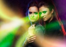 Female twins in colored light stripes. Royalty Free Stock Photo