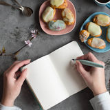 Female two hands hold a empty note. Designer draws sketches at the table coffee break. Hands with ink pen writing on notebook. Royalty Free Stock Photo