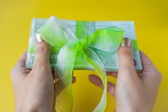 Female two hands holding a pack of hundred euro banknotes with green bow-knot, gift or dividends concept, european union money. Female two hands holding a pack stock photos