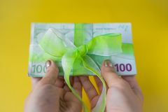 Female two hands holding a pack of hundred euro banknotes with green bow-knot, gift or dividends concept, european union money. Female two hands holding a pack royalty free stock photography