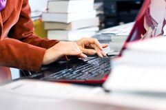 Female typing on laptop keyboard surrounded by books and files Stock Photo