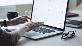 Female typing on laptop at workplace. Crop female hands typing on laptop while sitting at desktop with different objects on it stock footage