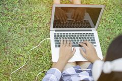 Female typing Thai keyboard of laptop and listening to the music by ear plug while sitting on green grass for relaxing in the par stock image