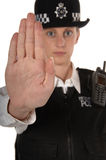 Female UK Police Officer STOP. Uniformed UK female police officer with hand up showing stop isolated on white focus on hand Stock Images