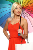 Female under umbrella holding shopping bag Stock Images