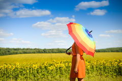 Female under umbrella standing in field of Stock Photos