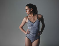 Female underwear model posing. Female fashion model posing on grey background. Caucasian woman wearing bodystocking looking away a copy space while standing with Stock Photography