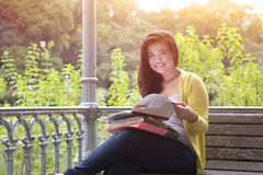 Female university student with books and files on lap. Beautiful young female university student with books and files on lap, sitting on wooden bench under Royalty Free Stock Images