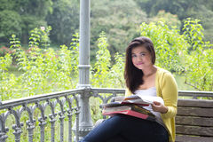 Female university student with books and files on lap in park. Beautiful young female university student with books and files on lap, sitting on wooden bench Royalty Free Stock Photography