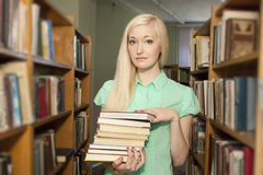 Female university student holding books in library Royalty Free Stock Photography