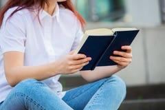 A confident student holding books over university building background. Female university student outdoors on Campus holding books. Confident student holding stock photography