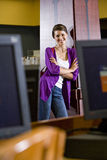 Female university student standing in library. Female university student standing in school library near computers Royalty Free Stock Photo