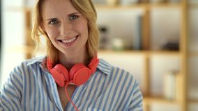 Female university student taking off headphones and smiling stock footage