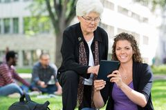 Female University Student Using Digital Tablet. Portrait of female university student using digital tablet with friend on campus park Stock Image